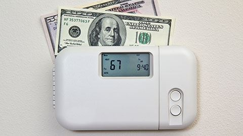 Thermostat with a 50 and 100 Dollar Bill